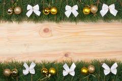 Weihnachtsrahmen gemacht von den Tannenzweigen verziert mit Weißbögen und goldenen Bällen auf einem hellen hölzernen Hintergrund Lizenzfreies Stockbild