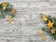 Weihnachtsrahmen - Kiefernniederlassungen und -sterne auf hölzernem Hintergrund lizenzfreie stockfotografie