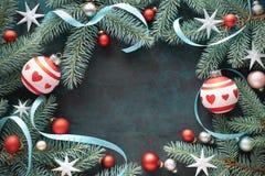 Weihnachtsrahmen mit den Tannenzweigen, den Trinkets im Rot und Silber, Stern Stockfoto