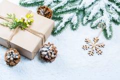 Weihnachtsrahmen mit Geschenk, den Niederlassungen des Weihnachtsbaums und den hölzernen Dekorationen auf Schneehintergrund Stockfoto