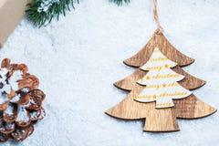 Weihnachtsrahmen mit Geschenk, den Niederlassungen des Weihnachtsbaums und den hölzernen Dekorationen auf Schneehintergrund Lizenzfreies Stockbild