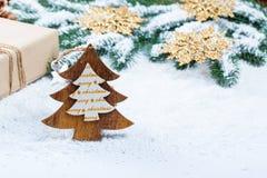 Weihnachtsrahmen mit Geschenk, den Niederlassungen des Weihnachtsbaums und den hölzernen Dekorationen auf Schneehintergrund Stockbilder