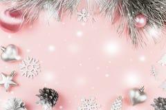 Weihnachtsrahmen mit Tannenzweigen, Nadelbaumkegeln, Weihnachtsbällen und silbernen Verzierungen auf Pastellrosahintergrund lizenzfreies stockbild