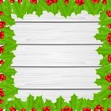 Weihnachtsrahmen von Stechpalmenbeeren auf hölzernem Hintergrund Stockbild