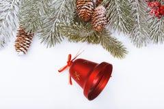 Weihnachtsrahmengrenze auf Weiß, Niederlassungen, Kegeln und roter Glocke Stockbild