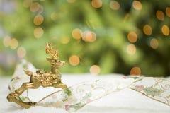Weihnachtsren-Verzierung, Band auf Schnee nahe funkelndem Lit-Baum Stockbilder