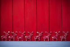 Weihnachtsrene auf rotem hölzernem Hintergrund Lizenzfreies Stockfoto