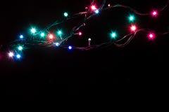 Weihnachtsromantische dekorative Girlande beleuchtet Rahmen auf schwarzem Hintergrund mit Kopienraum Lizenzfreies Stockbild