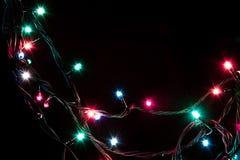 Weihnachtsromantische dekorative Girlande beleuchtet Rahmen auf schwarzem Hintergrund mit Kopienraum Stockbilder