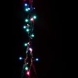 Weihnachtsromantische dekorative Girlande beleuchtet Rahmen auf schwarzem Hintergrund mit Kopienraum Stockfoto