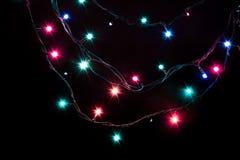 Weihnachtsromantische dekorative Girlande beleuchtet Rahmen auf schwarzem Hintergrund mit Kopienraum Stockfotografie