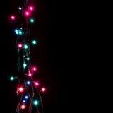 Weihnachtsromantische dekorative Girlande beleuchtet Rahmen auf schwarzem Hintergrund mit Kopienraum Lizenzfreie Stockfotografie