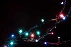 Weihnachtsromantische dekorative Girlande beleuchtet Rahmen auf schwarzem Hintergrund mit Kopienraum Lizenzfreie Stockbilder