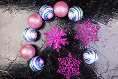 Weihnachtsrosa und purpurrote Bälle und dekorative Schneeflocken auf schwarzem Hintergrund Flache Lage Stockfotos