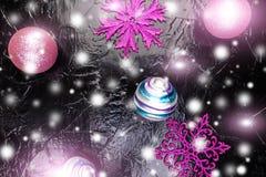 Weihnachtsrosa und purpurrote Bälle und dekorative Schneeflocken auf schwarzem Hintergrund Flache Lage Lizenzfreies Stockfoto