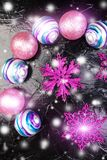 Weihnachtsrosa und purpurrote Bälle und dekorative Schneeflocken auf schwarzem Hintergrund Flache Lage Stockfoto