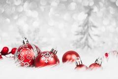 Weihnachtsrote Bälle mit silberner Dekoration auf dem Schnee Stockbild