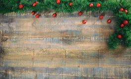 Weihnachtsrote Bälle und Girlande auf einem hölzernen Brett, Kopienraum Lizenzfreies Stockbild