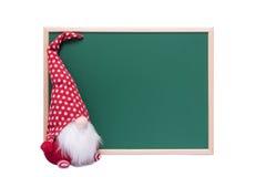 Weihnachtsrote Elfe mit dem langen weißen Bart, der neben einem leeren sitzt Lizenzfreie Stockfotos