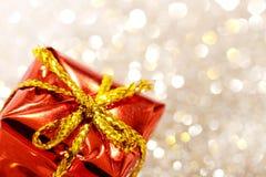 Weihnachtsrote Geschenkbox mit gelbem Bogen auf Funkelnsilber- und -goldhintergrund Lizenzfreies Stockfoto