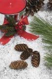 Weihnachtsrote Kerzen-und -kiefern-Kegel lizenzfreie stockbilder
