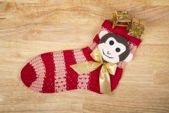 Weihnachtsrote Socke mit Affen und irgendwelche Geschenke lokalisiert auf Holzoberfläche Lizenzfreie Stockbilder