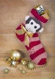 Weihnachtsrote Socke mit Affen und irgendwelche Goldkugeln lokalisiert auf Holzoberfläche Lizenzfreies Stockbild