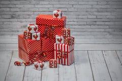 Weihnachtsrote und weiße Geschenke und Kasten auf grauem Hintergrund lizenzfreie stockbilder
