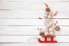 Weihnachtsroter Pferdeschlitten angetrieben durch Geschenkbox, goldene Kegel, Ausläufer stockfotos