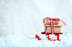 Weihnachtsroter Spielzeugschlitten mit einem Stapel von Geschenken Stockbild