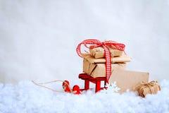 Weihnachtsroter Spielzeugschlitten mit einem Stapel von Geschenken, Papiertag Lizenzfreie Stockfotos