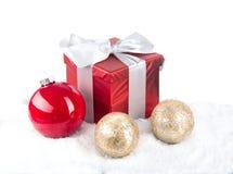 Weihnachtsrotes Geschenk mit festlichen Dekorationen auf Schneehintergrund Stockfotos