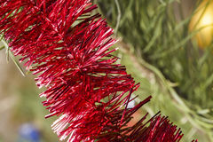 Weihnachtsrotes Lametta auf Baum Stockfotografie