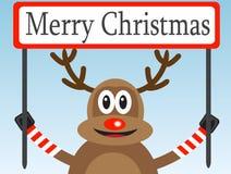 Weihnachtsrotwild mit einem Glückwunschplakat Stockfotografie