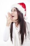 Weihnachtsruf durch schöne Frau mit Sankt-Hut Stockfoto