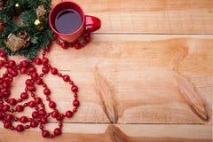 Weihnachtsrunde Girlande nahe einem roten Becher von heißem Lizenzfreie Stockbilder