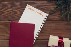 Weihnachtsrustikaler hölzerner Hintergrund mit Tannenbaumasten und einem Notizbuch Stockfotos