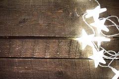 Weihnachtsrustikaler Hintergrund mit Lichtern, Schneeflocken, Sterne und Stockbild