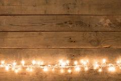 Weihnachtsrustikaler Hintergrund - Weinlese planked Holz mit Lichtern und Raum des freien Texts stockfotografie