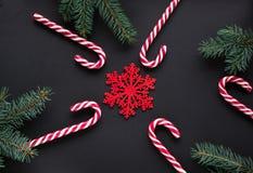 Weihnachtssüßigkeit mit silbernem Band, grüner Tannenbaum, Schneeflocke auf schwarzem Hintergrund Abstraktes Hintergrundmuster de Stockbild