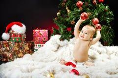 Weihnachtsschätzchen, das auf Pelz mit Geschenken sitzt Stockfotos