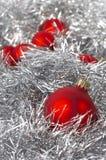 Weihnachtsschöne rote Bälle auf silbernem Hintergrund Stockfotos