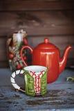 Weihnachtsschale und roter Teetopf auf Holztisch Stockfotos