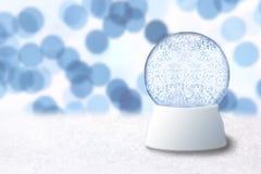 Weihnachtsschnee-Kugel mit blauem Feiertags-Hintergrund Lizenzfreies Stockbild