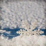 Weihnachtsschneeflocken auf einem schneebedeckten Hintergrund Lizenzfreie Stockfotos