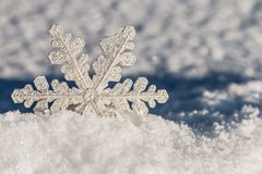 Weihnachtsschneeflocken auf einem schneebedeckten Hintergrund Lizenzfreies Stockbild