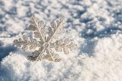Weihnachtsschneeflocken auf einem schneebedeckten Hintergrund Lizenzfreie Stockbilder