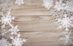 Weihnachtsschneeflocken auf hölzernem Hintergrund Stockbilder