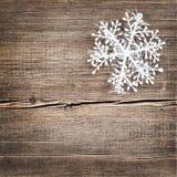 Weihnachtsschneeflocken auf hölzernem Hintergrund Stockfotografie