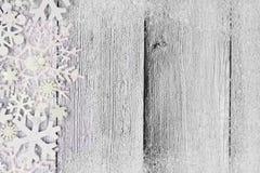 Weihnachtsschneeflocken-Seitengrenze mit Schneerahmen auf weißem Holz Stockfotografie